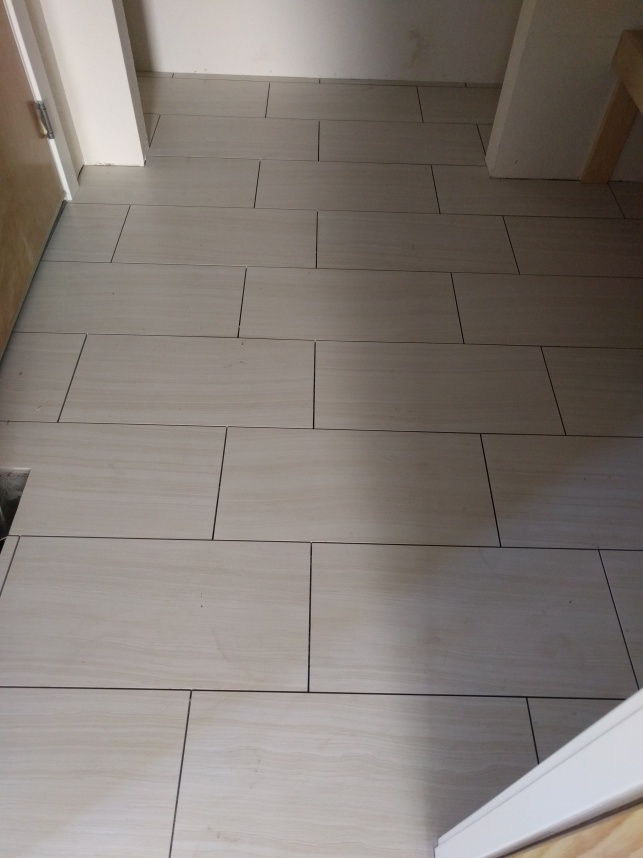 Floor tiling in the owners entry between the garage and hall